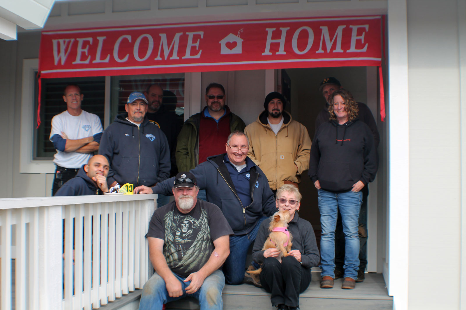 The Prestige Homes & Remodel crew and subcontractors in front of Jacque's newly rebuilt home in Coffee Park.